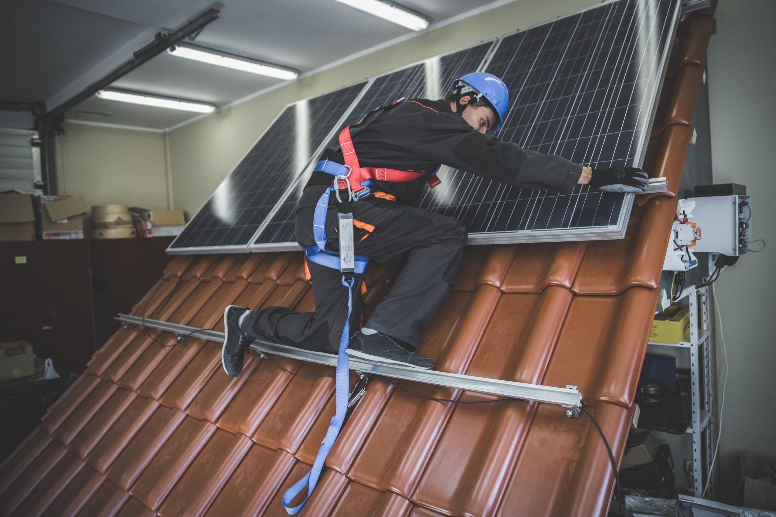 Montaż modułów PV na dachu ceramicznym przez wykładowcę w odzieży ochronnej
